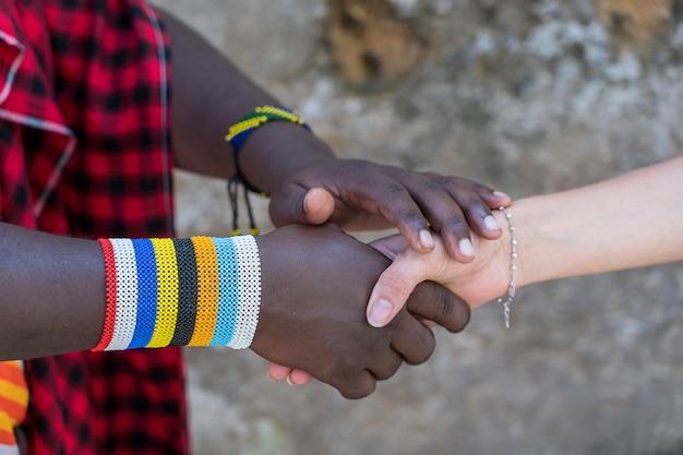 Homem tribal masai com uma garota fazendo um aperto de mão na rua na ilha de zanzibar