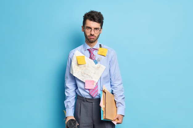 Homem triste com a barba por fazer olha seriamente para a câmera segurando café e papéis cansado de preparar relatório vestido com roupas formais chega para reunião de negócios