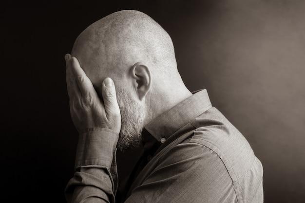Homem triste com as mãos fechadas, rosto virado para longe da luz. desespero e depressão. vergonha e culpa. tristeza e exílio