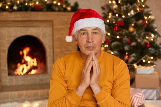 Homem triste com macacão laranja e chapéu de papai noel sentado no chão perto da lareira e decorando um pinheiro