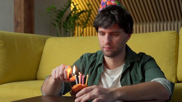 Homem triste comemora aniversário sozinho na sala, apagando as velas do bolo