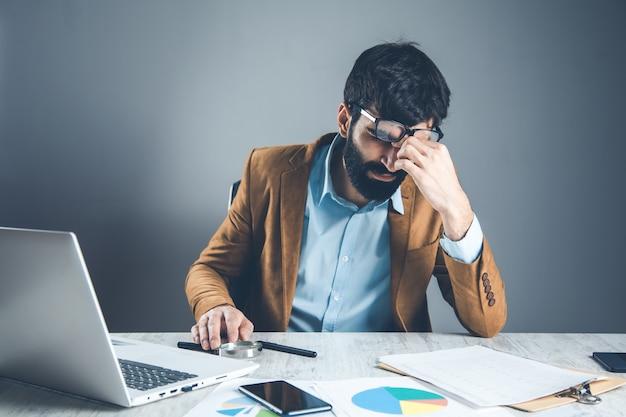 Homem triste de mãos dadas na mesa do escritório