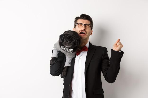 Homem triste de terno, segurando o cachorro pequeno bonito no ombro e chorando com cara de decepção, angustiado de pé sobre um fundo branco.