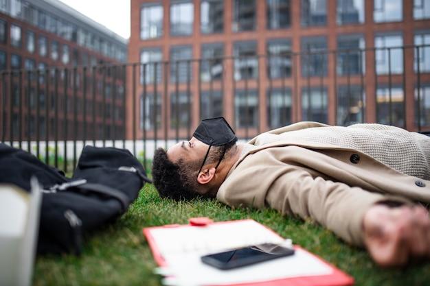 Homem triste e chateado com laptop deitado ao ar livre no parque no conceito de cidade, coronavírus e trabalho.