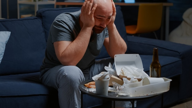Homem triste e deprimido sentado no sofá, desesperadamente, fadiga, solidão