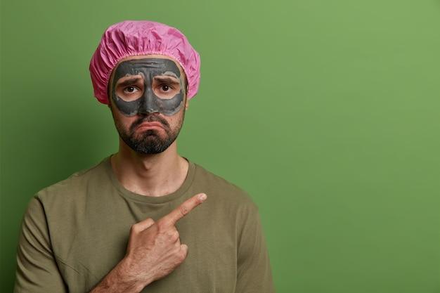 Homem triste e triste com expressão insatisfeita, aplica máscara de lama no rosto para cuidar da pele, usa touca de banho na cabeça, mostra algo desagradável, indica no canto superior direito na parede verde