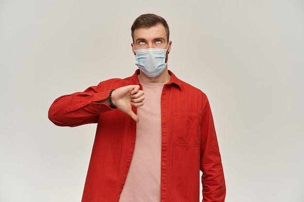 Homem triste entediado com barba em uma camisa vermelha e máscara higiênica para evitar infecção, olhando para cima e mostrando os polegares para baixo sobre a parede branca