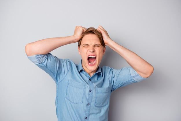 Homem triste indignado, estudante cometeu um erro em seu relatório se sentiu exausto perder a paciência gritar segurar o cabelo vestir roupas bonitas isoladas sobre parede de cor cinza