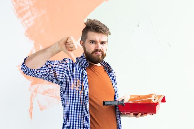 Homem triste mostrando o polegar para baixo, parede interior de pintura masculina com rolo de pintura na casa nova. cara com