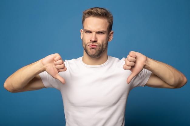 Homem triste mostrando os polegares para baixo isolado no azul