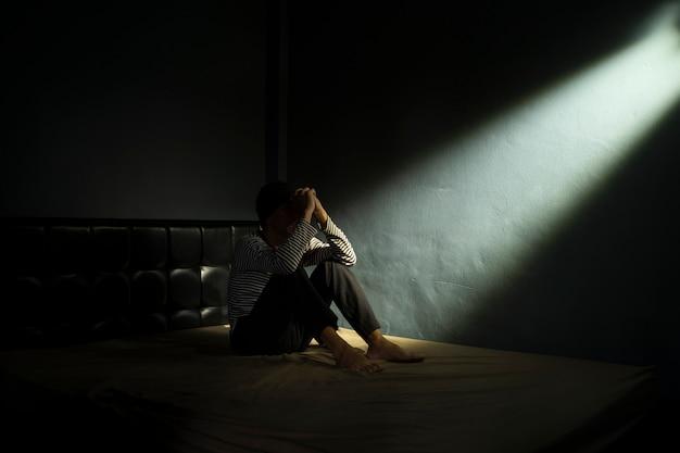 Homem triste no quarto escuro