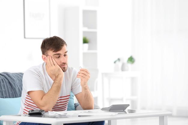 Homem triste segurando a aliança de casamento em casa. problemas de relacionamento