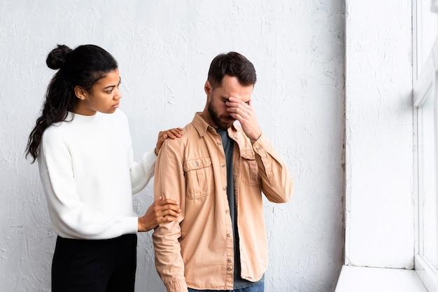 Homem triste sendo consolado por mulher em sessão de terapia em grupo