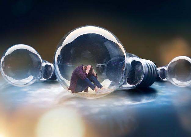 Homem triste sentado em uma lâmpada grande, efeito de escala