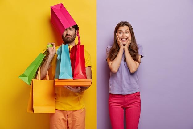 Homem triste sobrecarregado de sacolas de compras, esposa viciada em compras, passa o tempo livre durante o fim de semana comprando roupas novas