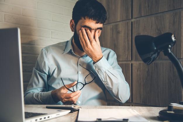 Homem triste trabalhando na mesa do escritório