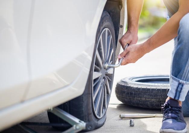 Homem trocando o pneu do carro com a chave de roda na rua, técnico que conserta o pneu com a chave, conceitos de reparação e manutenção