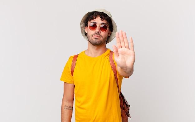 Homem turista hispânico parecendo sério, severo, descontente e irritado, mostrando a palma da mão aberta fazendo gesto de pare