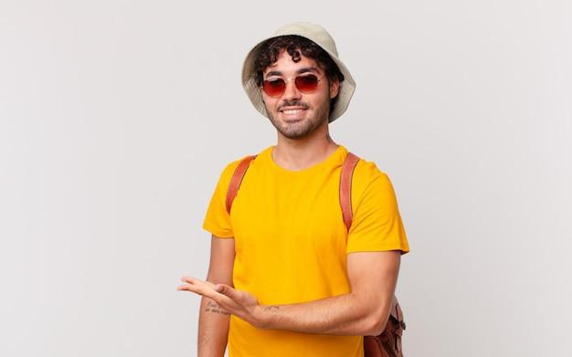 Homem turista hispânico sorrindo alegremente, se sentindo feliz e mostrando um conceito no espaço da cópia com a palma da mão