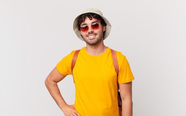 Homem turista hispânico sorrindo feliz com uma mão no quadril e uma atitude confiante, positiva, orgulhosa e amigável