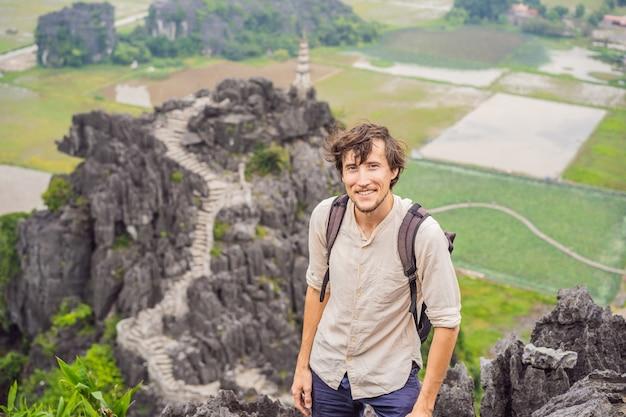 Homem turista no topo do pagode dos campos de arroz do templo hang mua ninh binh vietnã vietnã reabre fronteiras