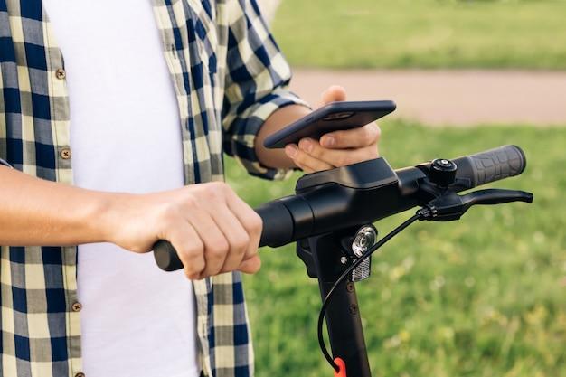 Homem turista pega scooter elétrico ao compartilhar aplicativo de telefone turístico de estacionamento