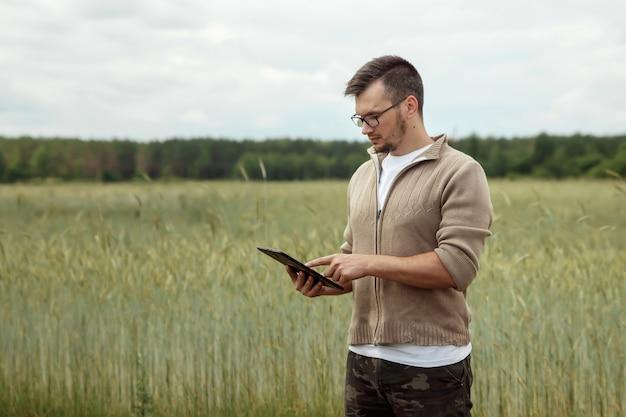 Homem um agricultor em pé no campo e usando um tablet.