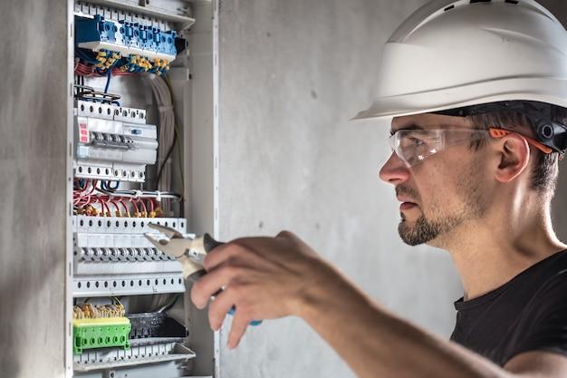 Homem, um técnico elétrico que trabalha em um painel de distribuição com fusíveis. instalação e conexão de equipamentos elétricos.