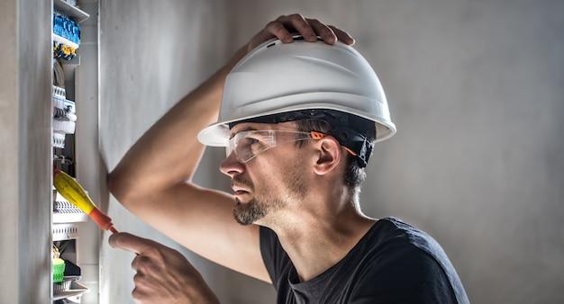 Homem, um técnico elétrico trabalhando em um painel de distribuição com fusíveis. instalação e conexão de equipamentos elétricos.