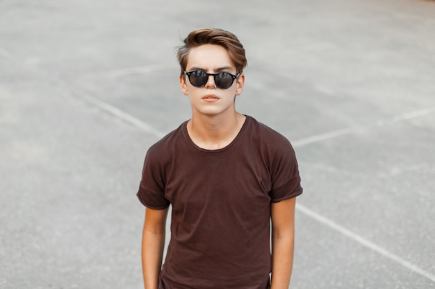 Homem urbano na moda jovem hippie em uma camiseta marrom elegante com penteado em óculos de sol pretos da moda fica no estádio