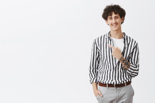 Homem urbano simpático, relaxado e descontraído, com tatuagens de bigode e cabelo encaracolado apontando para o canto superior esquerdo, sorrindo com um olhar satisfeito e encantado em uma camisa legal listrada