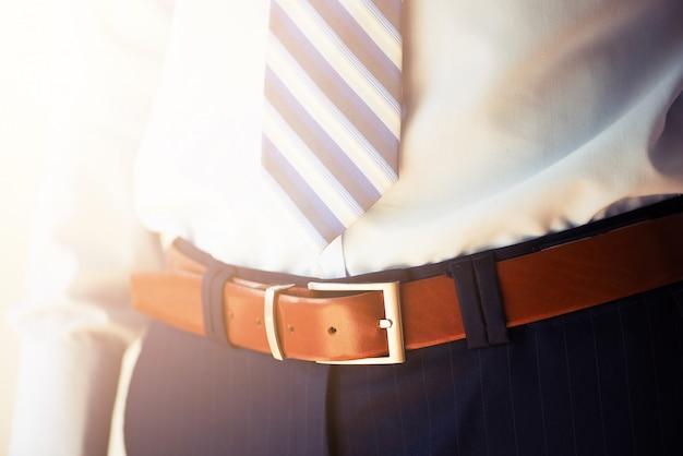Homem usa cinto. jovem empresário de terno casual com acessórios. conceito de moda e vestuário. noivo se preparando na manhã antes da cerimônia