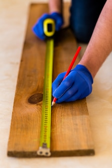 Homem usa fita métrica na madeira