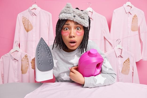 Homem usa máscara de dormir e pijama segura uma garrafa de detergente e ferro elétrico faz poses domésticas perto da tábua de passar
