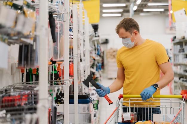 Homem usa máscara e luvas de proteção médica, impede o coronavírus, segura o machado