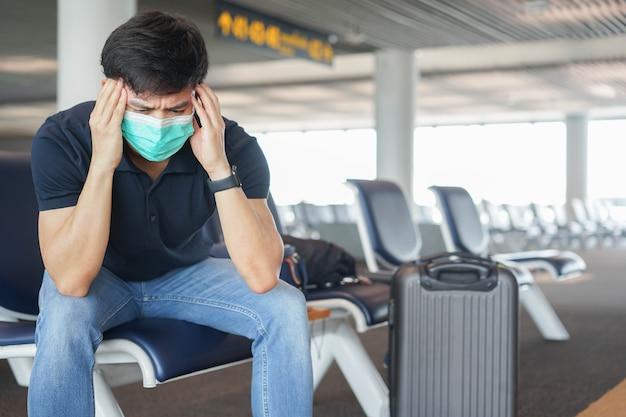 Homem usa máscara facial e sente dor de cabeça enquanto está sentado no portão do aeroporto esperando o horário de embarque