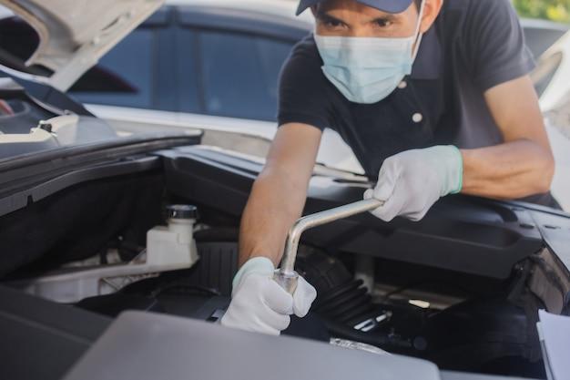 Homem usa máscara facial trabalho serviço reparo e manutenção de automóveis, reparador mãos consertando motor de carro oficina automotiva mecânico de automóveis