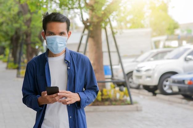 Homem usa máscara facial usando smartphone móvel