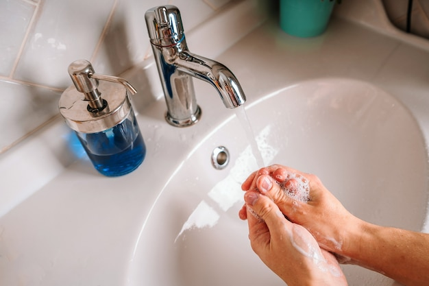 Homem usa sabão e lava as mãos debaixo da torneira. detalhe do conceito de higiene para mãos