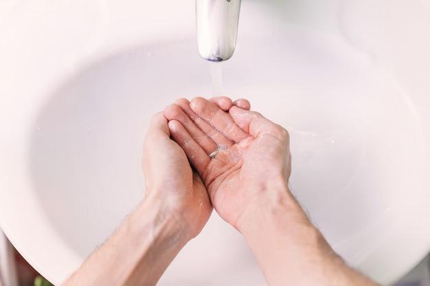 Homem usa sabão e lavar as mãos sob a torneira de água