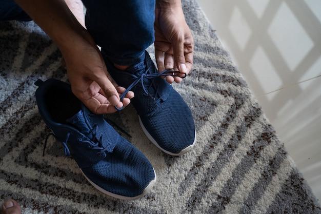 Homem usa sapatos no quarto no tapete
