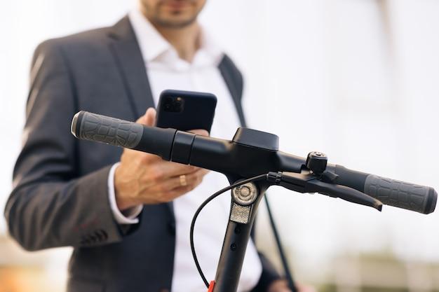 Homem usa scooter elétrico como meio de transporte moderno na cidade um empresário do sexo masculino