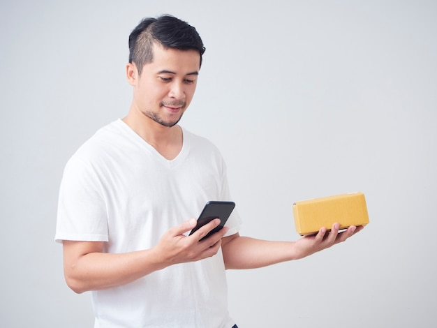 Homem usa smartphone e caixa aberta
