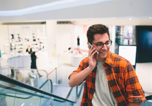 Homem usa smartphone em shopping