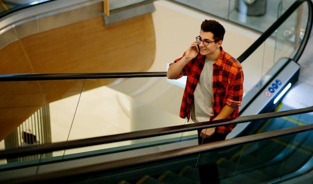 Homem usa smartphone na parede do shopping