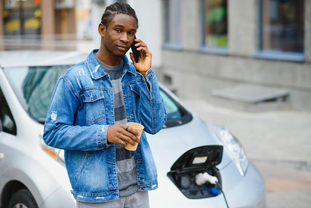 Homem usa telefone inteligente enquanto espera e a fonte de alimentação se conecta a veículos elétricos para carregar a bateria no carro