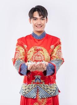 Homem usa terno cheongsam sorrindo e se levantando para dar o dinheiro do presente para sua família