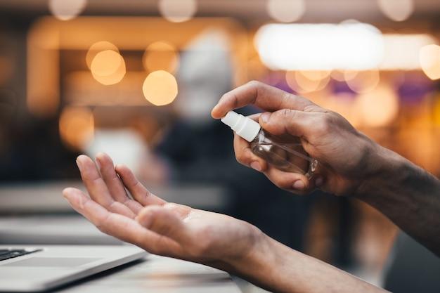 Homem usa um spray anti-séptico para as mãos.