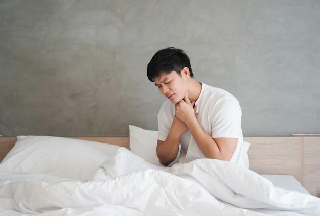 Homem usando a mão para tocar o pescoço com dor de garganta depois de acordar