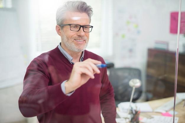 Homem usando a parede de vidro para escrever algumas informações